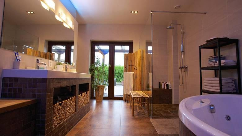 LUKSUS: Badet har samme gjennomgående tema, men her er betongen byttet ut med fliser på gulvet. Store vinduer gir lys inn og istedenfor gardiner har de et stort skjermbrett i bambus. FOTO: Irene Jacobsen