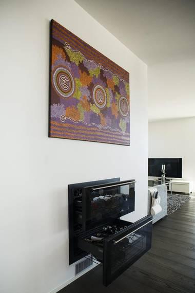 FRA AUSTRALIA: Familien har vært på ferie i Australia og bildet er tradisjonell aboriginer-kunst. Det symboliserer vannkilder og energi. Under er et integrert vinskap i to etasjer. FOTO: Elias Dahlen