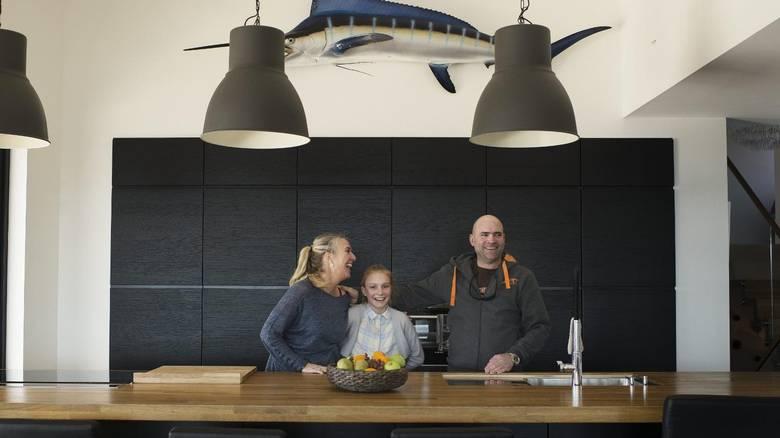 ØYEN: Her samles Susanne, Agatha Cöllstina og Osaac Lekven familie og venner for å lage mat. Kjøleskap og oppbevaring skjules i den svarte veggen. Det er også ekstra kjøleskap og fryser i eget lagringsrom. Fisken på veggen er en kopi av en fisk Isaac fikk på stang i USA. FOTO: Elias Dahlen