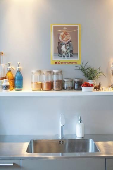 ORIGINAL OPPVASK: Kjøkkenbenken og servanten er uten skjøter og er bestilt fra Danmark. Hyllen over vasken har elementer fra ulike verdensdeler, som vitage vannflasker fra Buenos Aires, et motiv med gul innramming fra Bangkok og nostalgiske norgesglass. FOTO: FILIPPA TREDAL