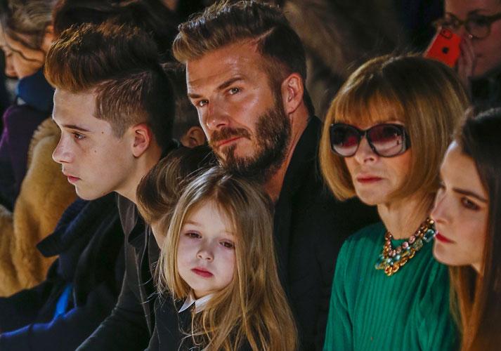 HELDIG LITEN FRØKEN: David Beckham sitter ed siden av Vogue-sjefen Anna Wintour sammen med sin datter, Harper, og sønnen Brooklyn. Bildet er tatt under New York Fashion Week tidligere i år. FOTO: REUTERS