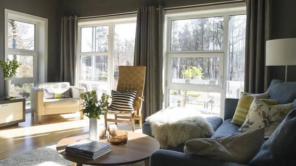 LYST. De store vinduene slipper inn mye lys, og gjør at leiligheten oppleves luftig selv om den er malt mørk. Den klassiske stolen, designet av Bruno Mathsson, har hun overtatt av sin far. FOTO: BØRRE ESKEDAHL