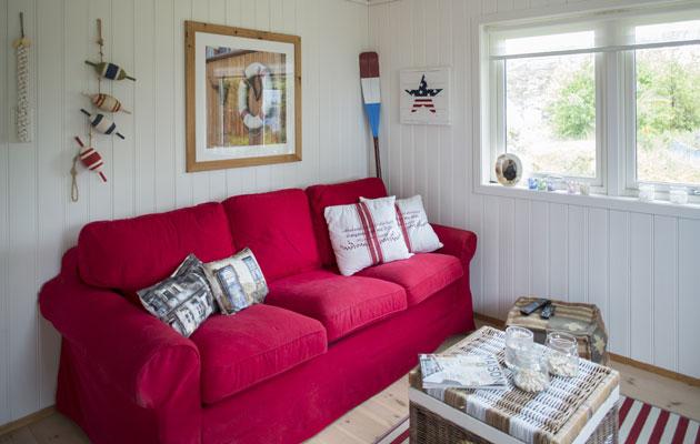 RØDT: Da Sirens bror ble kjøpt ut, skapte de et soverom om til TV-stue, med rød sofa og maritim twist. FOTO: Jan M. Lillebø