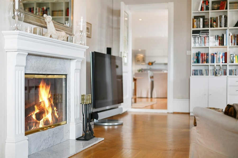VINTERKOS: Det er flere ildsteder i huset, blant annet en hvit kakkelovn som strekker seg fra gulv til tak. FOTO: Privatmegleren Vikebø & Jørgensen