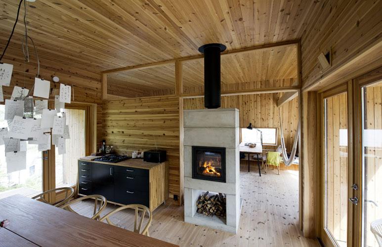 INNEKOS: Kjøkkenbordet er laget av to gulvplanker og kan lett flyttes dit man ønsker. Ovnen har glass på begge sider og varmer opp både stue og kjøkken. I lampen over kjøkkenbordet. FOTO: Helge Skodvin