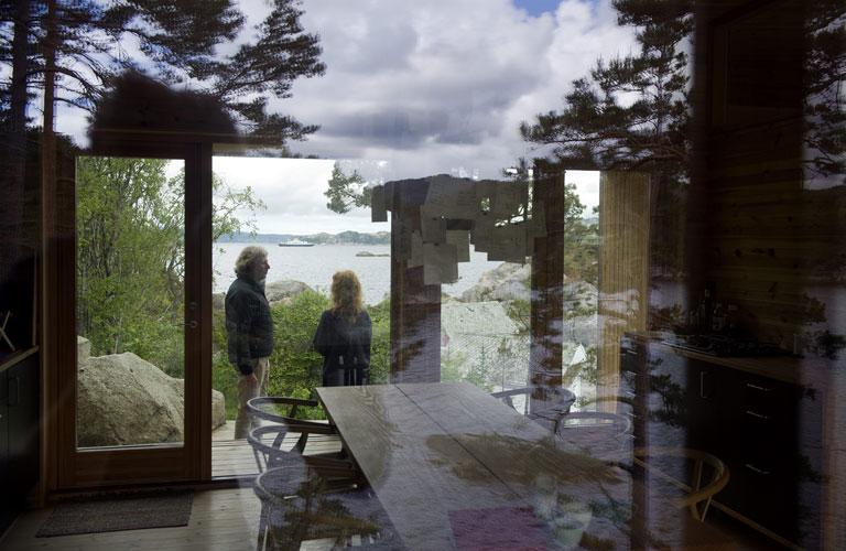 BINDER SAMMEN: Vinduer fra gulv til tak på begge sider av hytten slipper naturen inn. Både inne på kjøkkenet og ute er det god plass, og passer både til to og tjue gjester. FOTO: Helge Skodvin