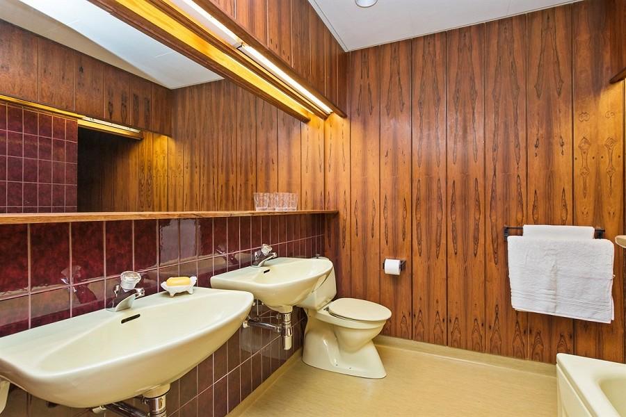 TEAK OG MAHOGNY: Til og med på badet holder man seg i det rundt 40 år gamle tiåret. FOTO: Privatmegleren