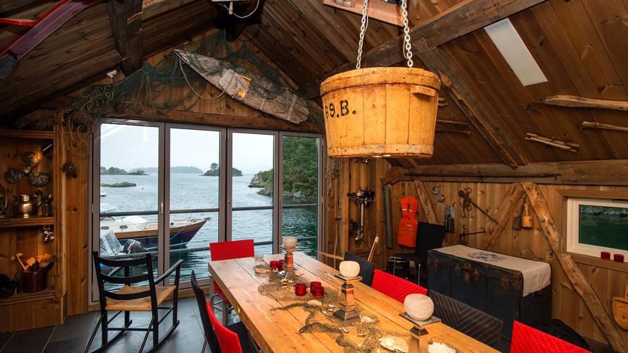 GAMMELT: Naustloftet er dekorert med gammelt fiske- og fangstutstyr fra Fedje, hvor Arne Dalseides mor vokste opp. Lampen over spisebordet er en gammel linestamp. FOTO: Rune Sævig